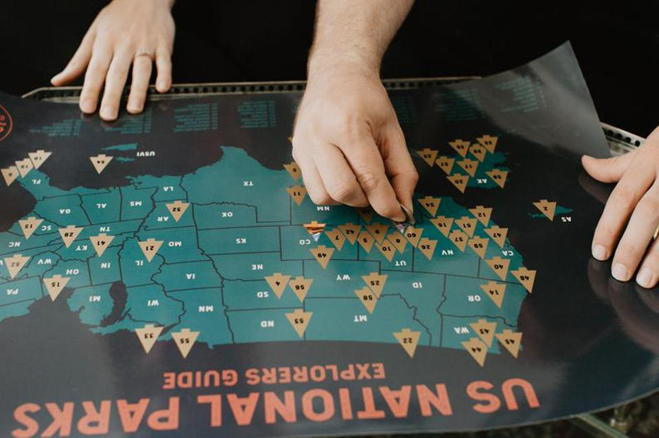 Hands scratch off the national park travel map