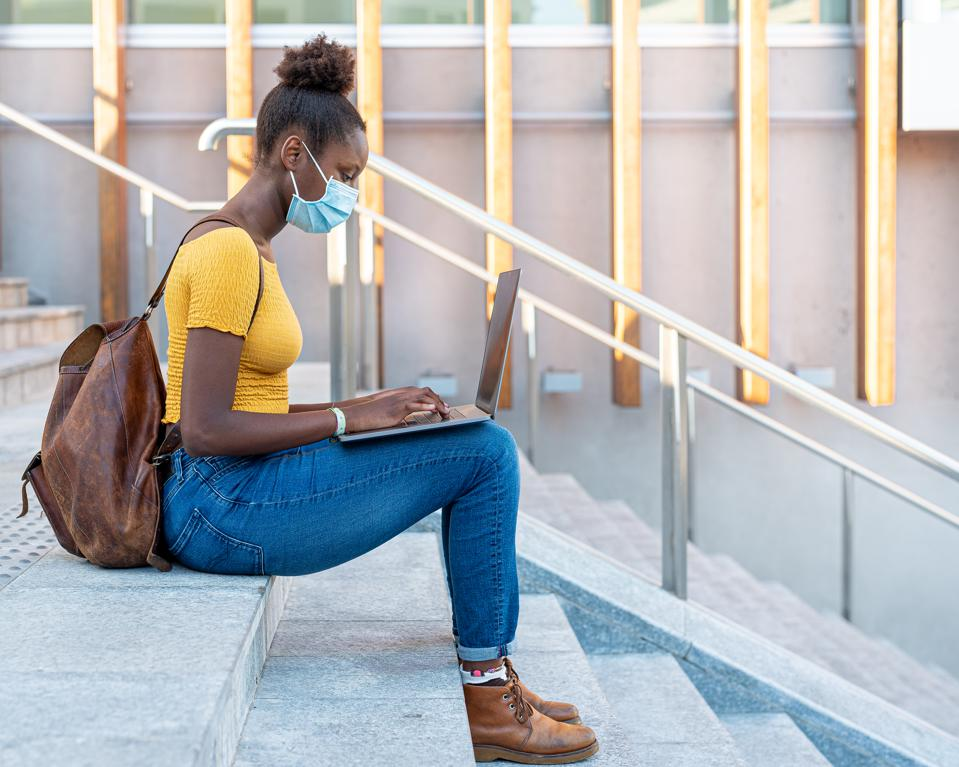 beautiful and young black girl who studies and works with a laptop around the city, blogger and smart worker in times of epidemic surf the internet, use multimedia content, use of protective mask in times of epidemic