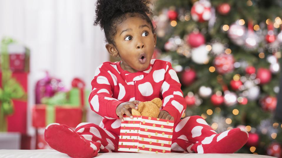 Surprised girl holding teddy bear toy on Christmas
