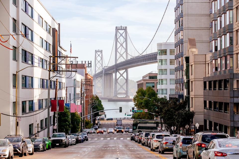 Street in downtown of San Francisco with San Francisco-Oakland Bay Bridge in the center, California, USA