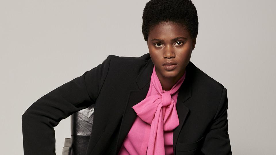 Woman wearing blazer and pink top looks at camera