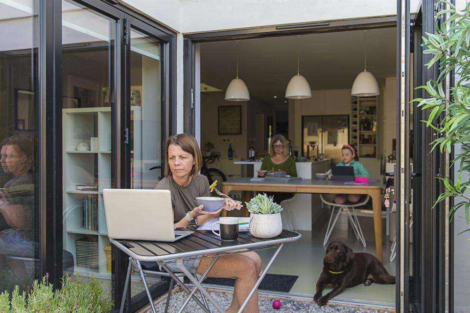 Woman working from home. Her family are eating lunch in the background