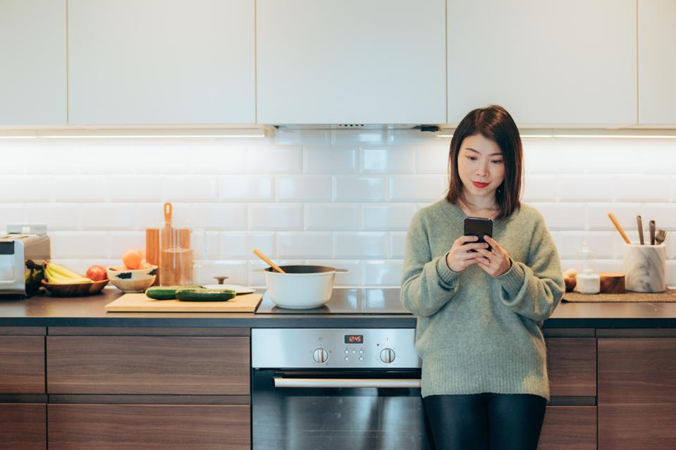 Young beautiful woman using phone standing and leaning on kitchen worktop