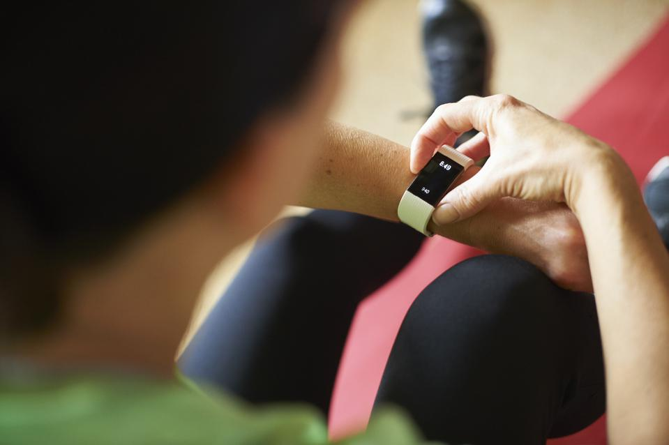 Woman exercising in her living room and looking at fitness watch