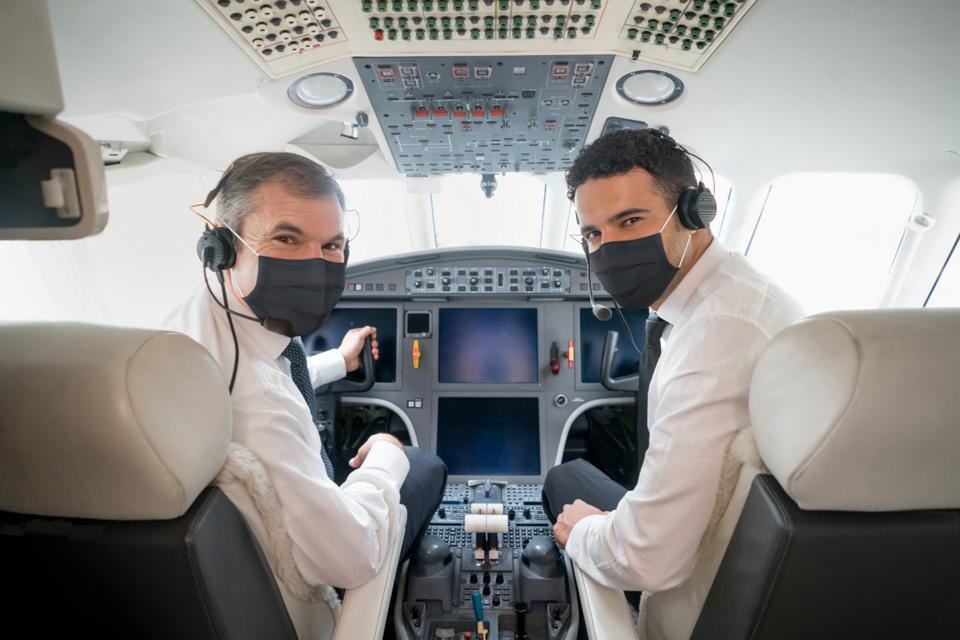 Pilots ready to fly an airplane and wearing a facemask while looking at the camera