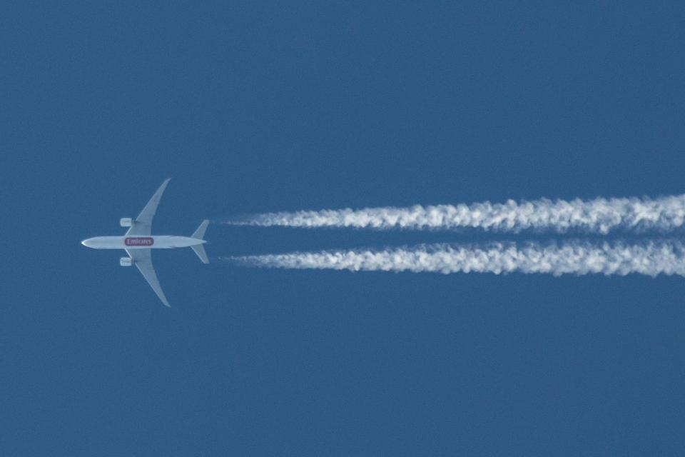 An Emirates Boeing 777F plane leaves visible contrails in the blue sky as it flies above Greece.