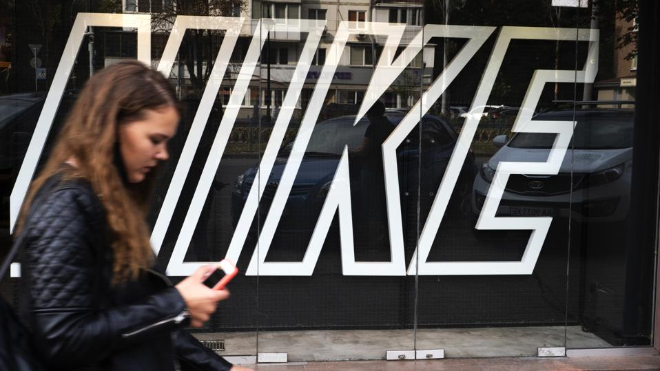 A woman with a smartphone walks past the Nike logo at one of the Nike stores.
