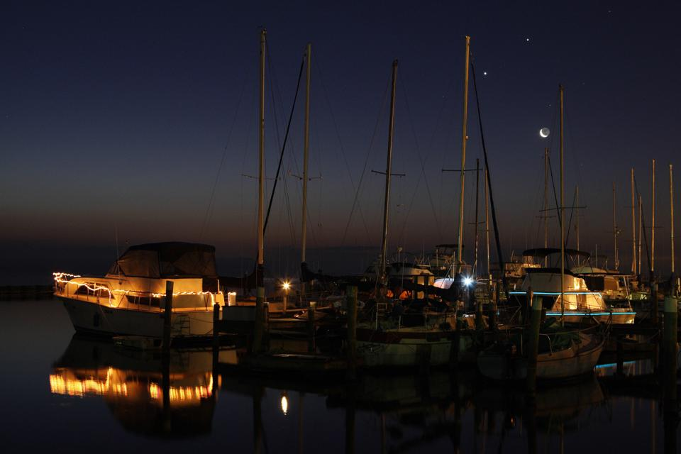 The crescent Moon rises with the planets Venus and Jupiter over boats in Florida.