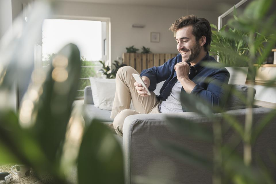 Young man sitting on couch at home, using smartphone