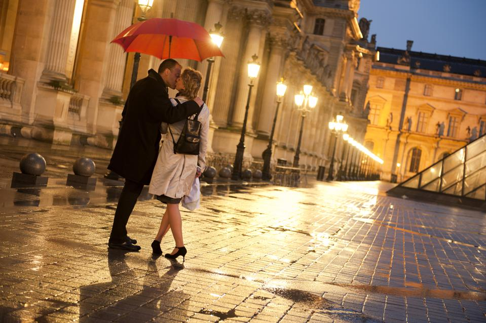 Couple kissing in rain at night at the Louvre