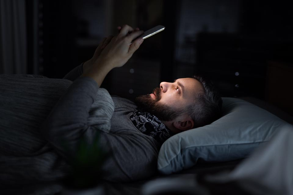 Ill mature man patient in bed at home at night, using smartphone.