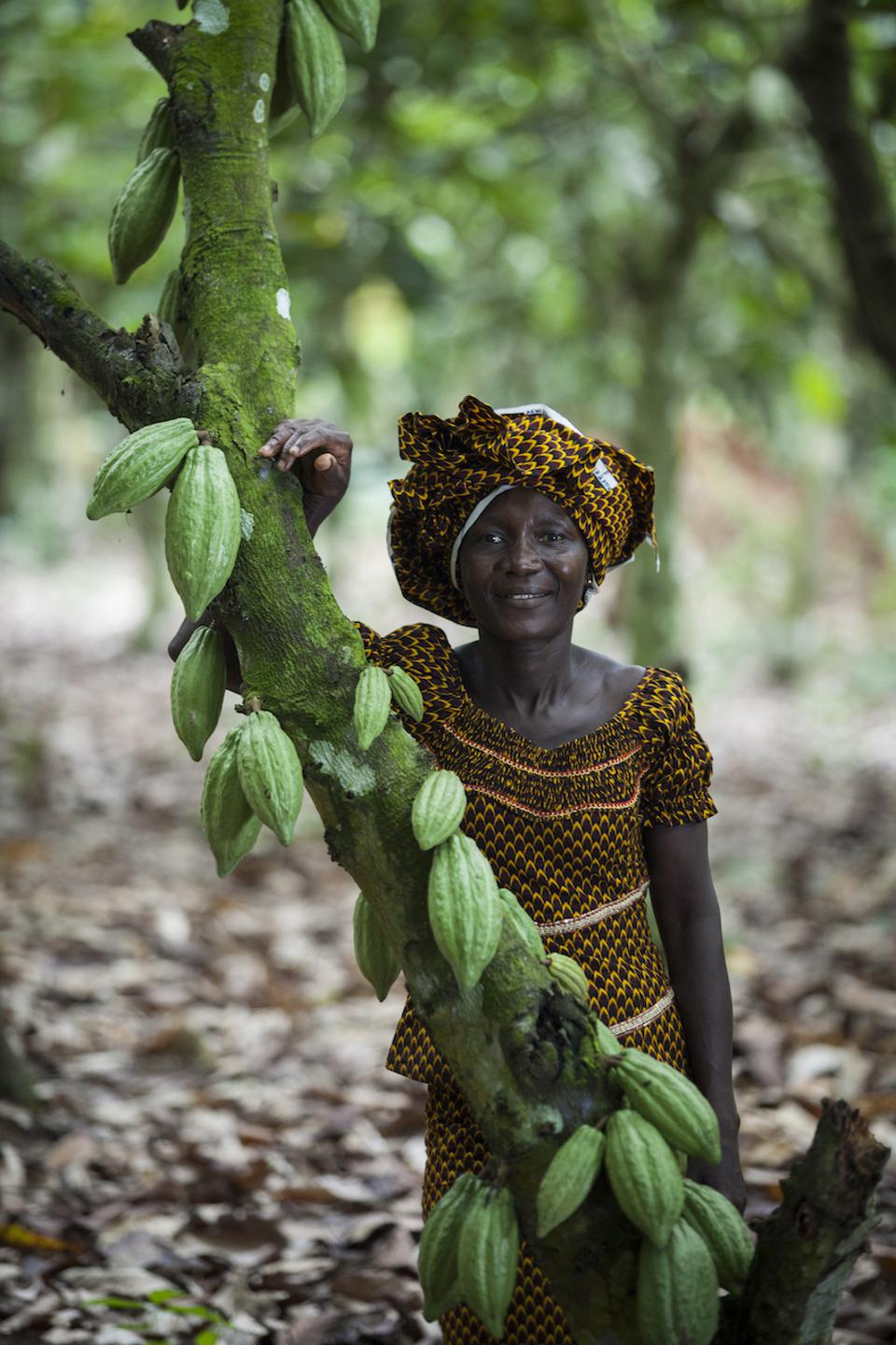 Alphonsine N'Guetia of Coopaza proudly stands next to a cocoa tree on her farm in Cote d'Ivoire. Coopaza is a Part of the Ben & Jerry's Living Income program.