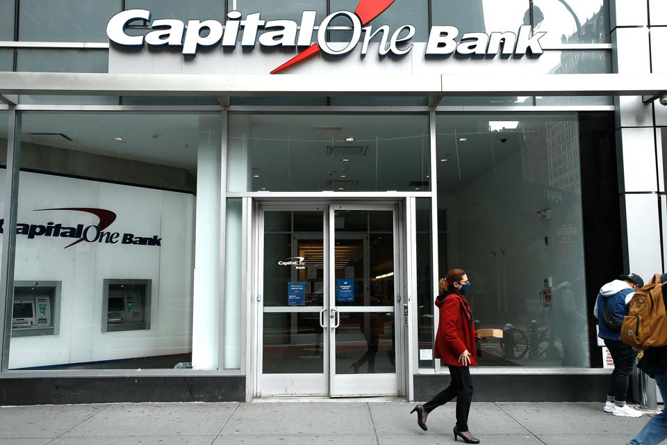 A woman wearing a face mask walks past the Capital One Bank...