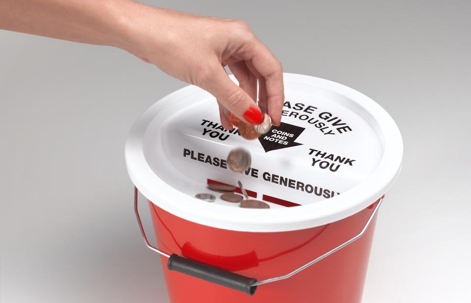 Coins being donated in charity bucket
