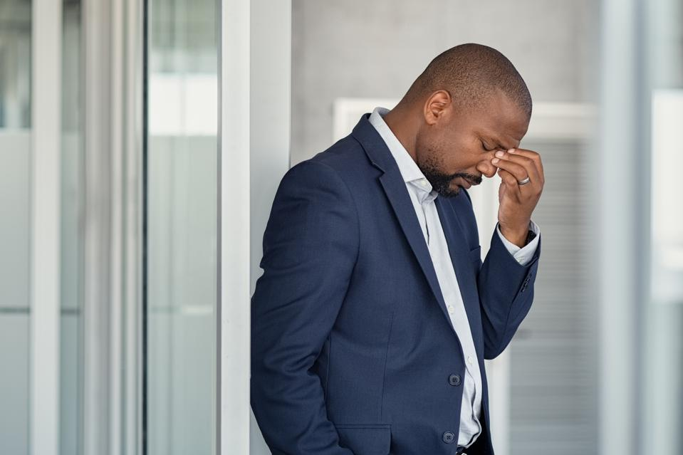 Stressed black businessman suffering from workplace microaggressions