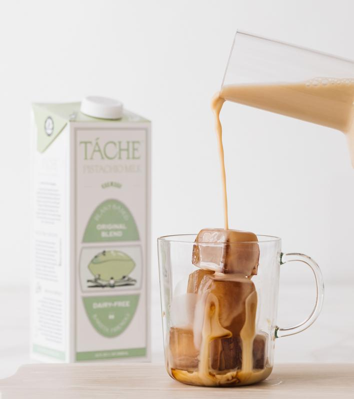 Táche pistachio milk poured into a glass with ice next to a carton