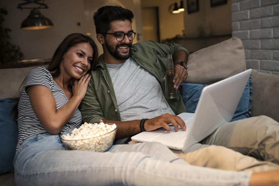 Young couple watching a movie on a laptop.