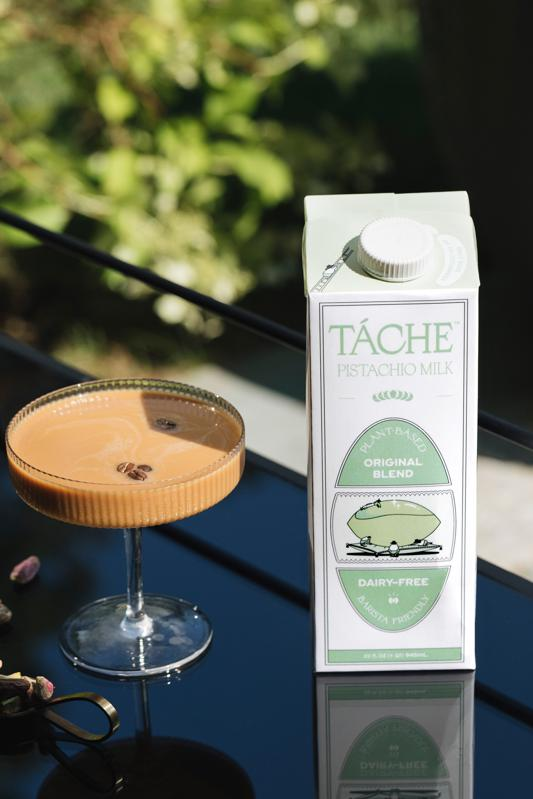 Táche pistachio milk next to drink