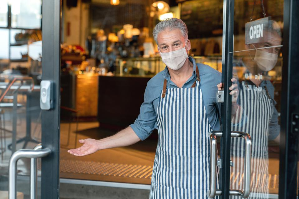 Business owner wearing a facemask and reopening his cafe after the quarantine