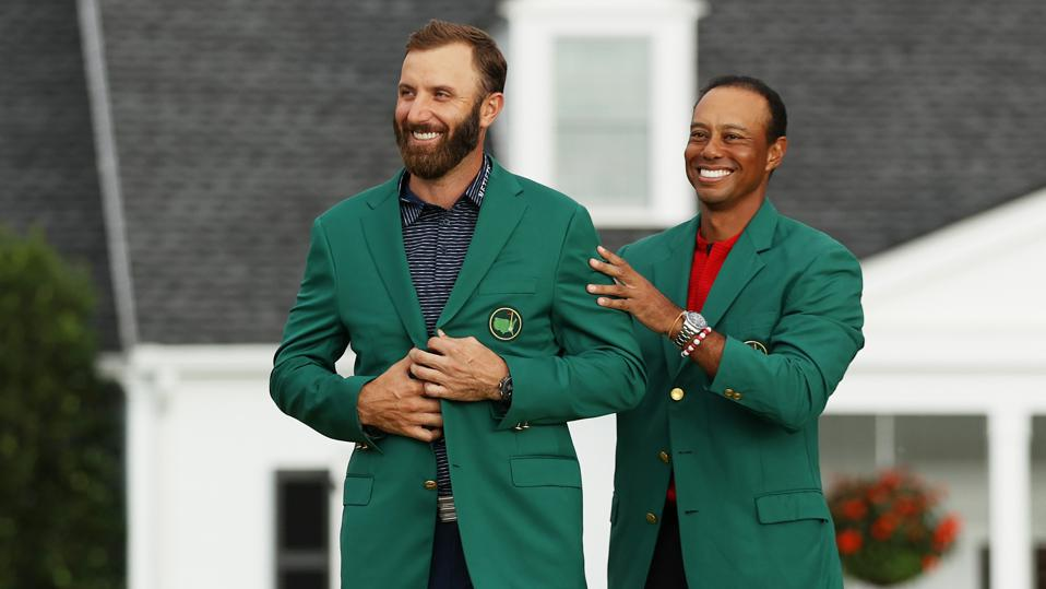 Dustin Johnson is awarded the Green Jacket by Masters champion Tiger Woods.