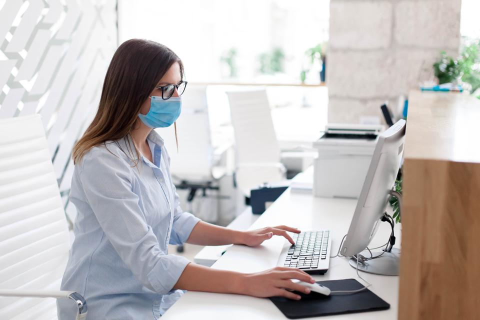 Young woman wearing medical mask in office. Protection employees on workplace. Girl working