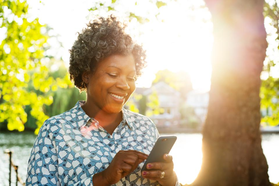 Smiling woman using smart phone outside