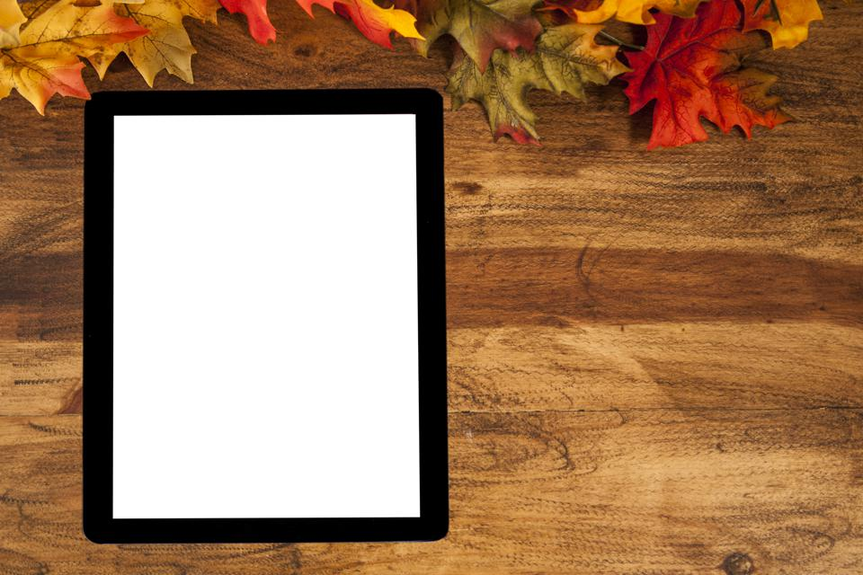 Blank digital tablet with autumn leaves.