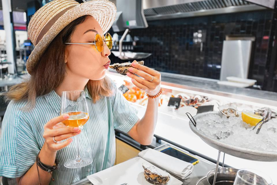 woman eating oyster and drinking wine in seafood restaurant