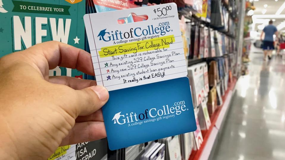 A gift card for a college savings account is held in hand in a department store.