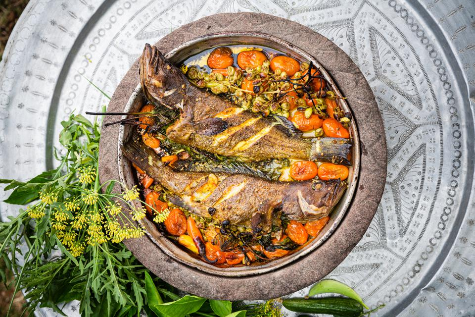 Closeup of whole fish surrounded by vegetables by chef Erez Komarovsky.