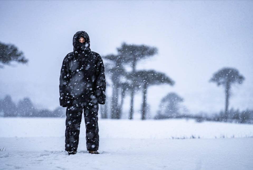 A man stands in the snow wearing a Selk'bag