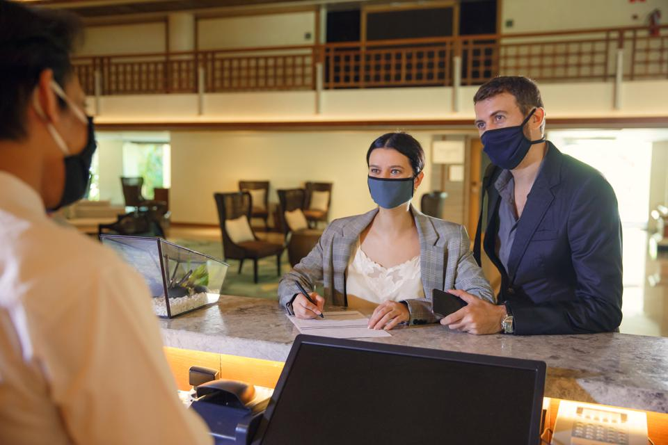 Couple and receptionist at counter in hotel wearing medical masks as precaution against virus. Couple on a business trip doing check-in at the hotel