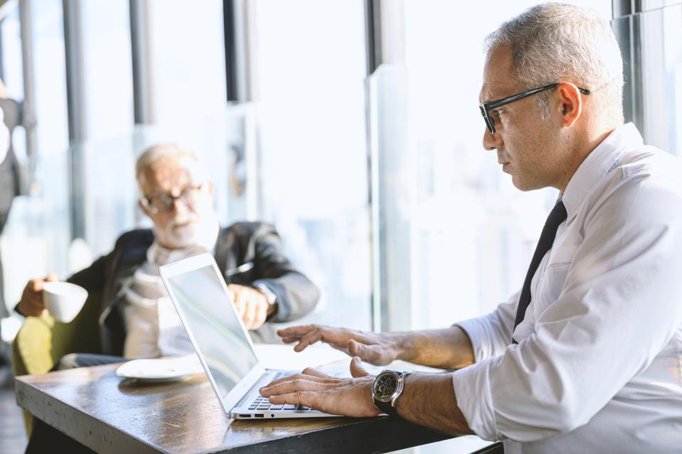 Portrait of Pensive mature businessman using laptop. Seinor man works on laptop, check e-mail, Online marketing.