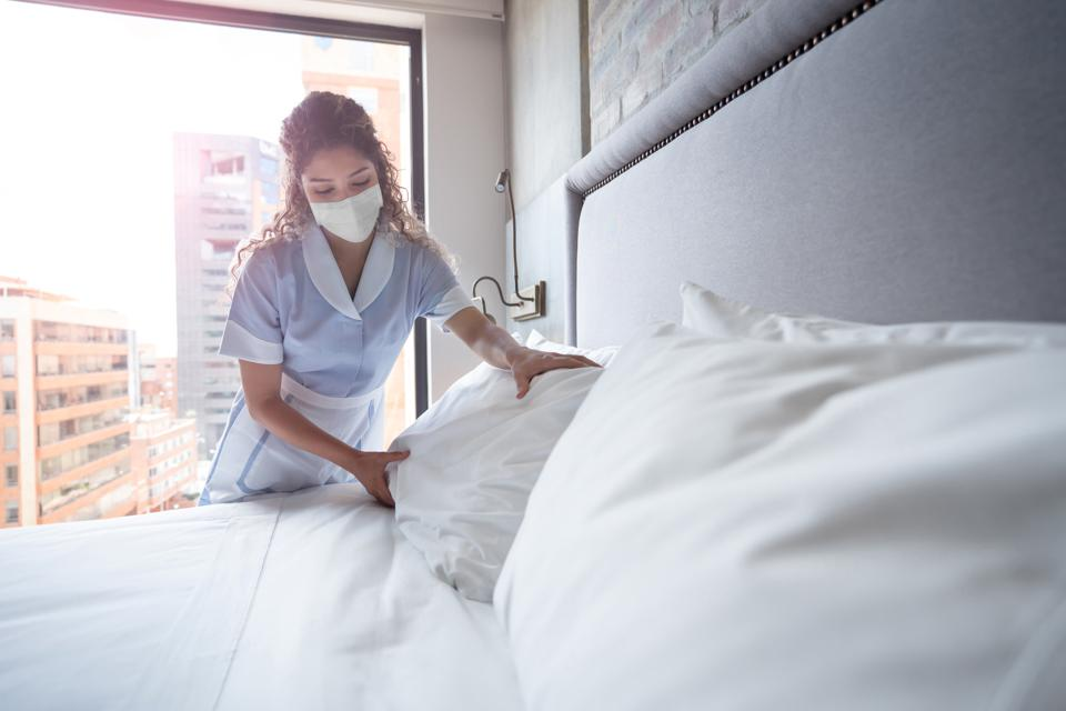 A hotel maid cleaning a room in a Norway hotel wearing a face mask.