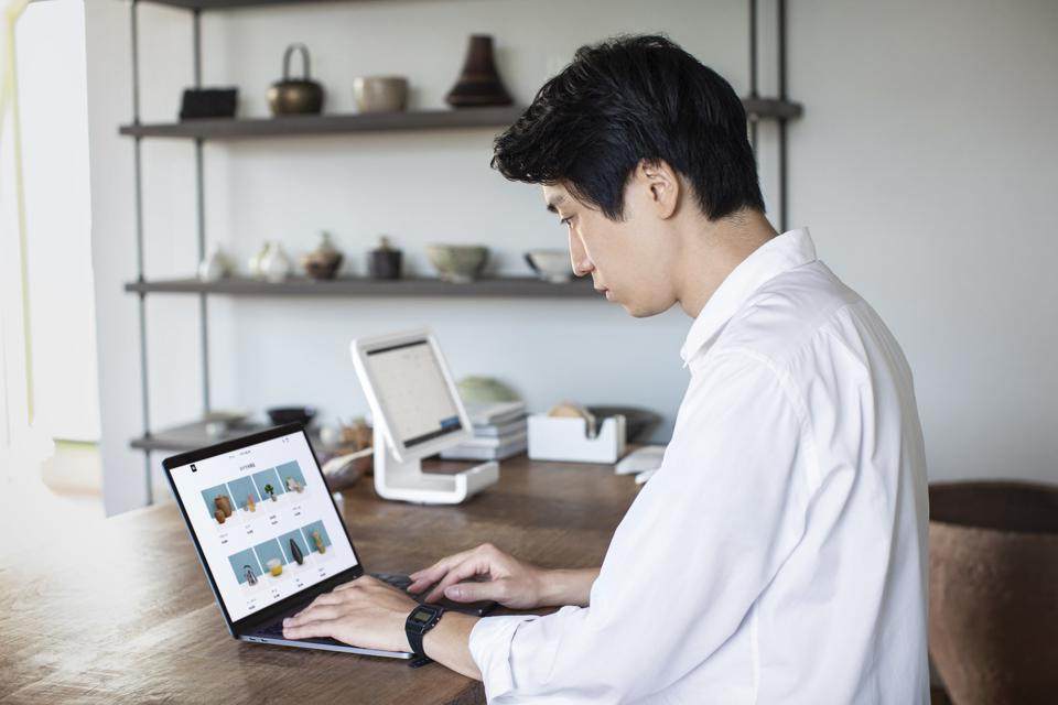 A business owner manages their online store from their laptop.