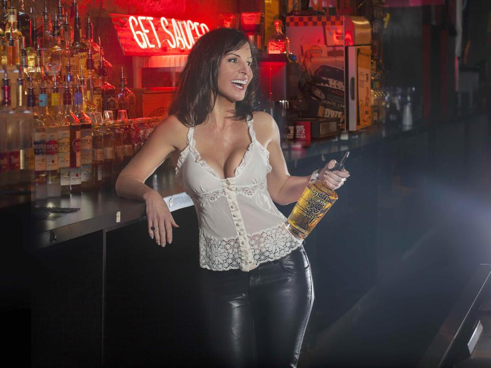 Lovell stands in front of a bar holding a bottle of booze.