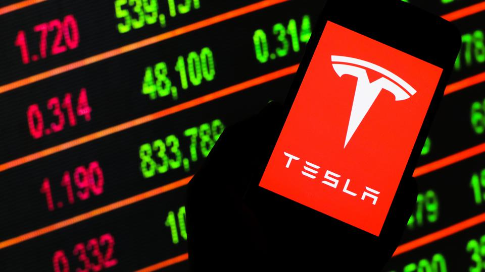 In this photo illustration a Tesla logo seen displayed on a...