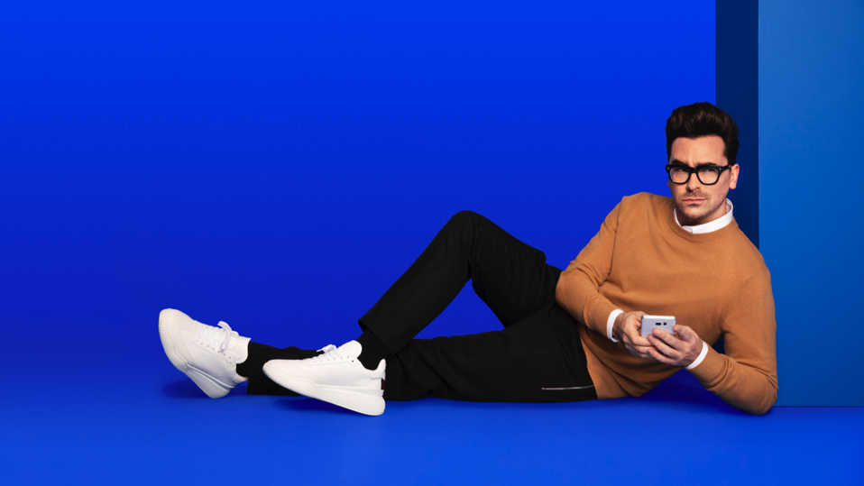 Dan Levy posing with a cell phone in his hand