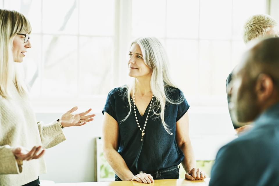 Smiling businesswoman listening to colleague during meeting in office conference room