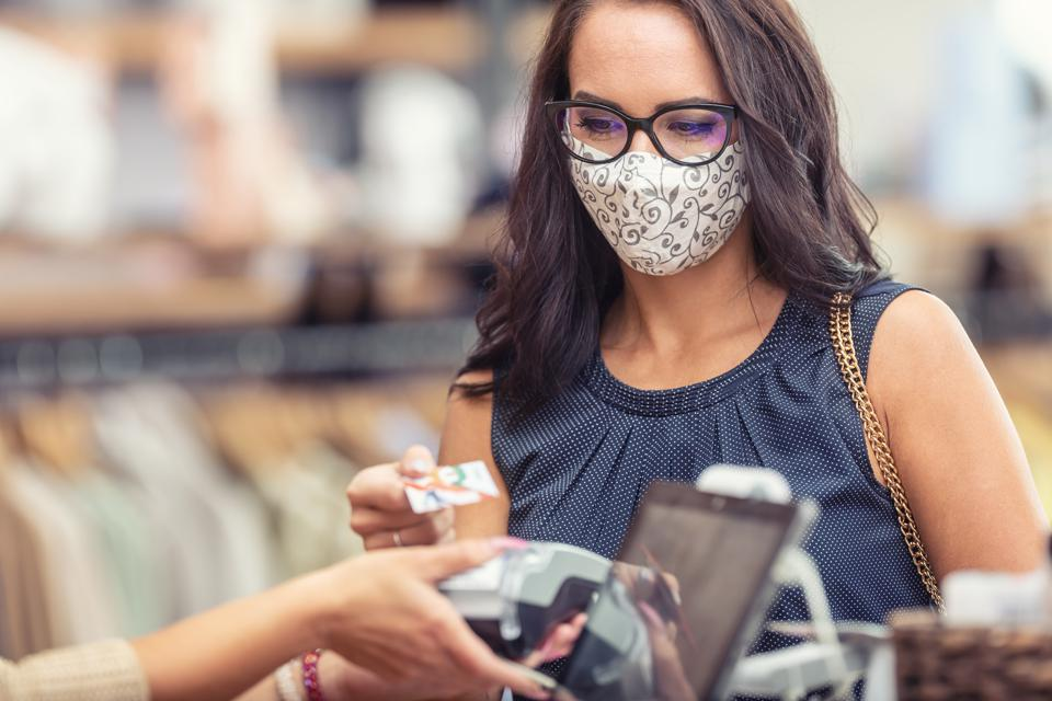 Face mask protection against Covid-19 and contactless payment in the shopping mall.