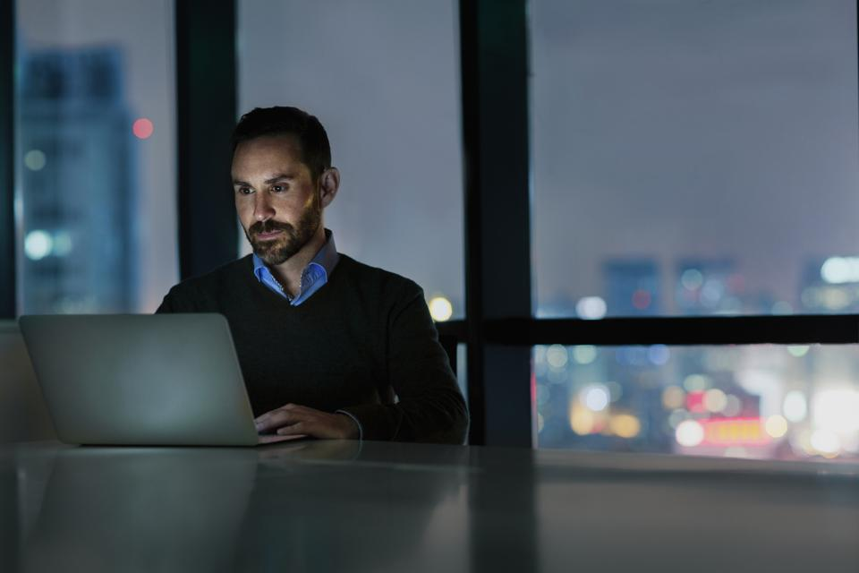 Man viewing laptop computer in office at night