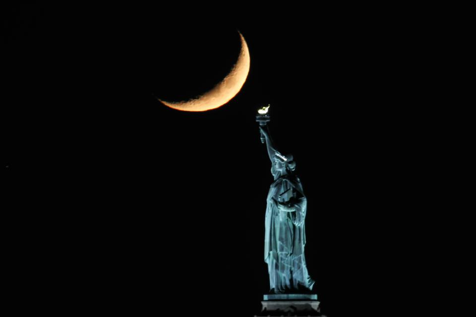 Crescent Moon sets behind the Statue of Liberty in NYC