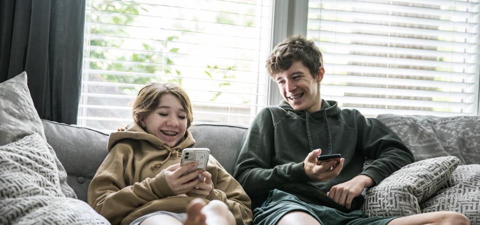 Teenage siblings looking at smartphones and laughing