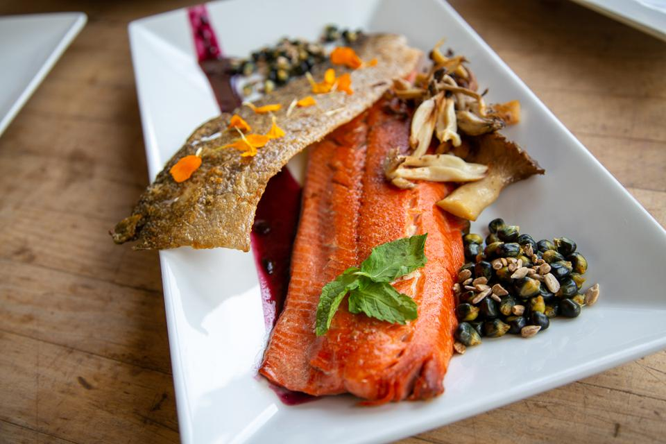 Plate of cooked salmon with mushrooms and blueberry sauce.