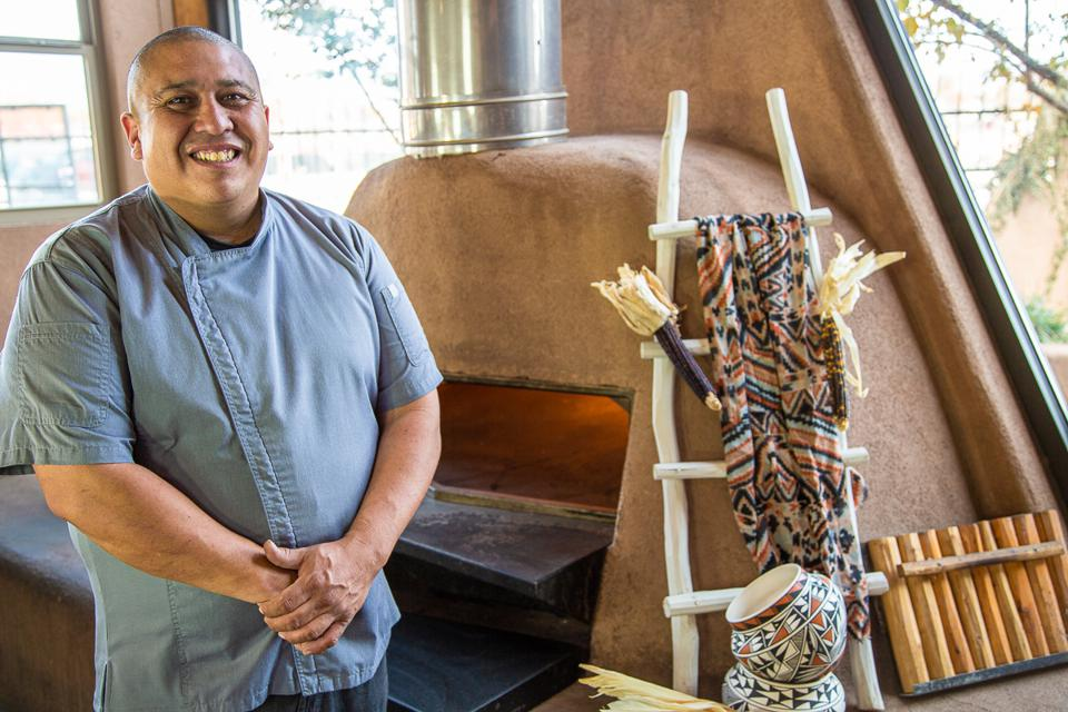 Executive chef Ray Naranjo standing next to a pante clay oven.