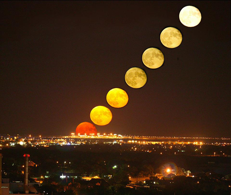 Timelapse of the Moon rising over city lights and a clear, flat horizon.