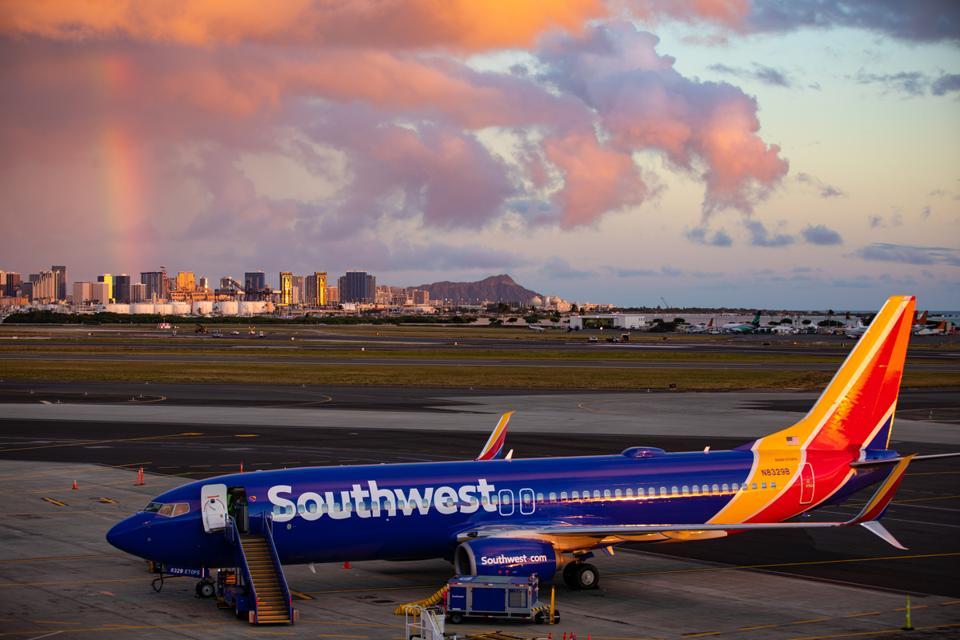 Southwest 737-800 unloads on runway with Oahu's Diamond Head in the distance.