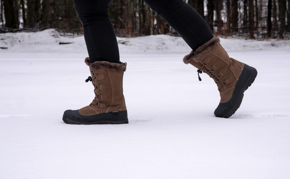 A woman walks through snow in a pair of Baffin boots