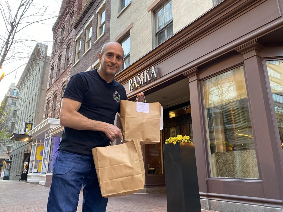 Joel Haas outside Washington, D.C. restaurant Rasika with a takeout order.