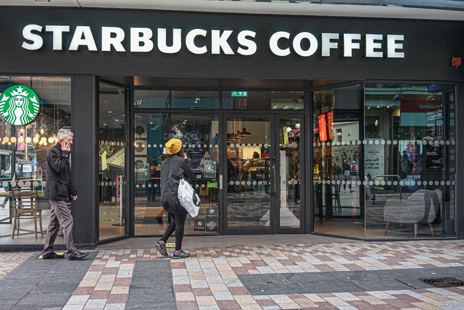 Customers wait outside the Starbucks Coffee Shop...